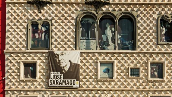 Faixa com retrato do autor figura na fachada da Fundação José Saramago, em Lisboa, um museu e instituição cultural dedicada à memória do escritor. [2]