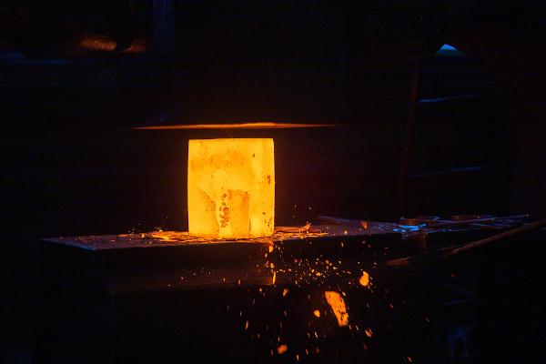 Bloco de metal sendo submetido a processo siderúrgico.