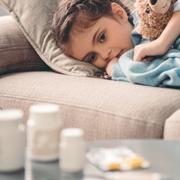 criança doente com remédios na sua frente