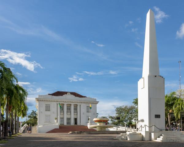 Foto do Palácio Rio Branco, com um chafariz à sua frente, em uma praça e rodeado de coqueiros.