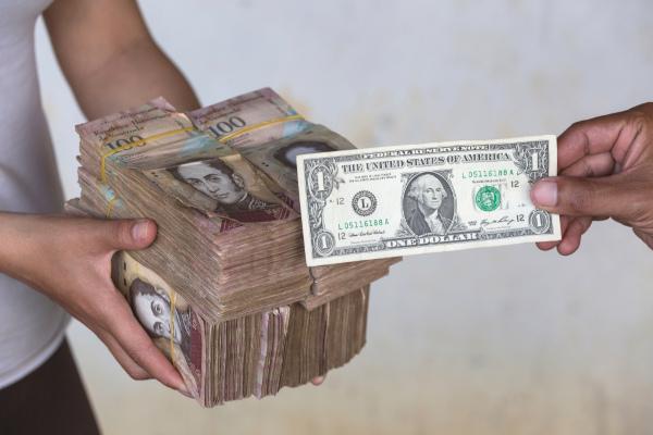 Mãos entregando 250.000 bolívares em troca de uma nota de um dólar.