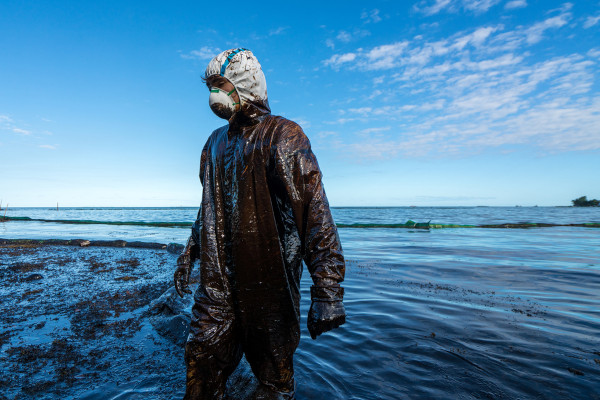 Foto de um homem, com roupas apropriadas e todo sujo, no oceano Índico, ajudando a limpar das águas uma mancha de petróleo.