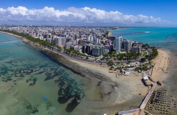 Foto de parte de Maceió vista de cima e composta por prédios rodeados pelo mar.
