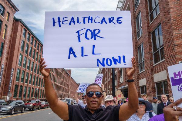 """Homem segura cartaz onde se lê: """"Healthcare for all now"""" (em tradução livre, """"Saúde para todos agora"""")."""