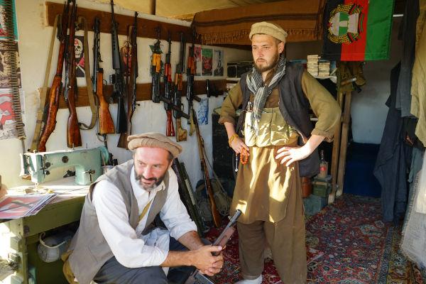 Membros do Talibã em um quarto cheio de armas.