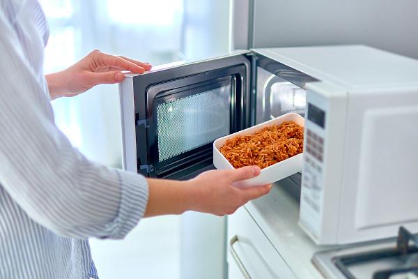 Pessoa inserindo alimento no aparelho de micro-ondas.