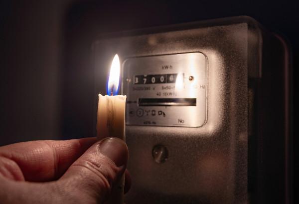 Mão segurando uma vela acesa iluminando o medidor do consumo de energia elétrica.