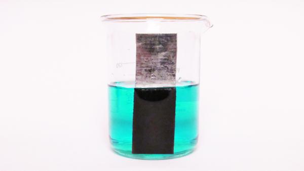 Placa de zinco dentro de uma solução de sulfato de cobre II, com formação de depósito escuro sobre a placa de zinco.