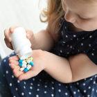 Criança com frasco de remédios