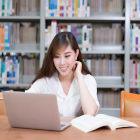 Aluna com notebook na biblioteca