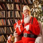 Papai Noel segura um presente vermelho com laço branco