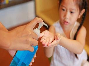 Criança usando álcool em gel