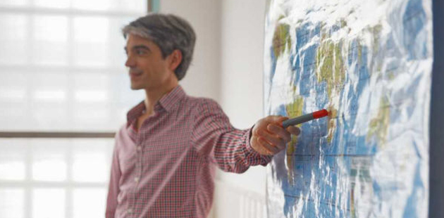 Homem apontando para mapa mundi