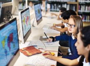 Crianças na frente de computadores que contém mapas na tela
