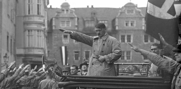 Hitler fazendo aceno nazista em cima ao redor de militares