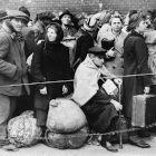 Refugiados com suas malas atrás de cerca