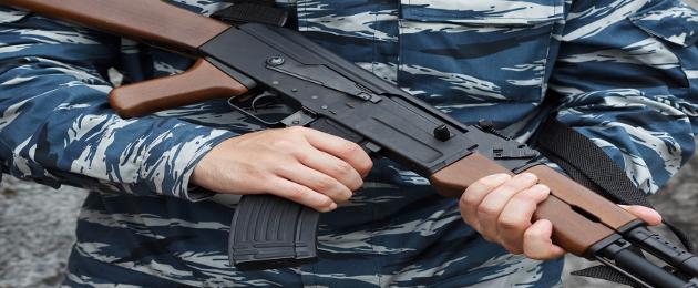 Homem fardado segurando arma