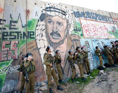 Soldados israelenses em frente ao muro que separa Israel da Cisjordânia, com grafite que retrata o líder palestino Yasser Arafat