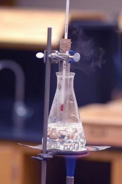 Experimento para determinar a entalpia de combustão. Acima temos a combustão completa (chama azul)