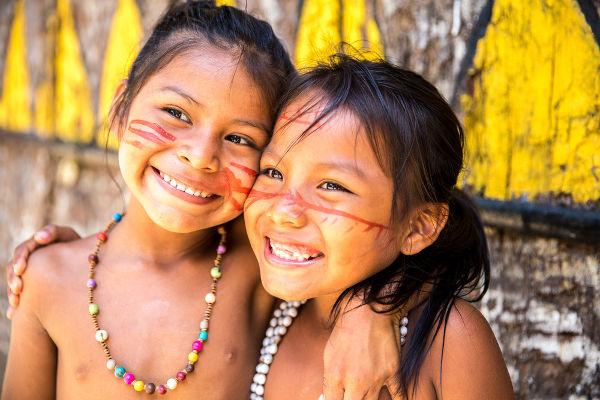 Crianças indígenas com pinturas tradicionais no rosto e colares típicos.
