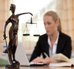 Estátua representando a justiça e advogada ao fundo embaçada