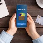 Mulher segurando celular indicando uma carteira digital na tela