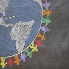 Desenho de globo terrestre envolvido por bonecos coloridos em quadro-negro escolar