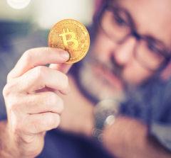 Homem desfocado segurando uma bitcoin (moeda amarela)